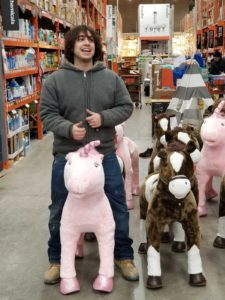 "Patrick's helper ""Vinegar"" Victor being silly, sitting on a toy unicorn at Home Depot"