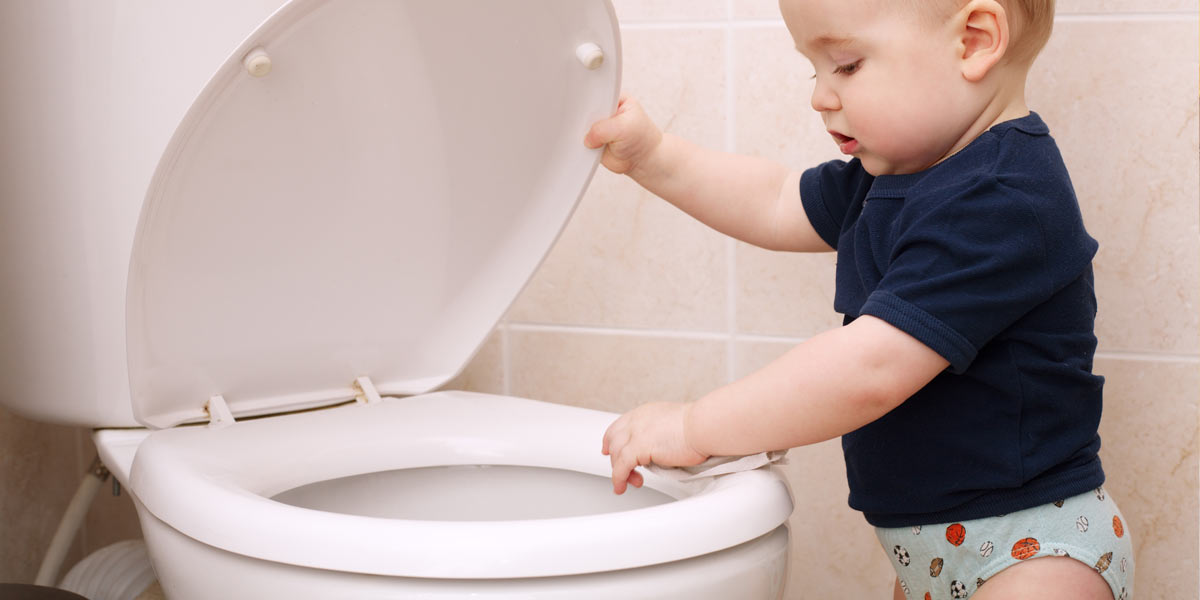 Toddler looking in toilet. Children's toys are often the cause of a clogged toilet.