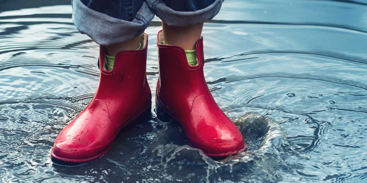 Woman wearing rubber boots because of a basement flood