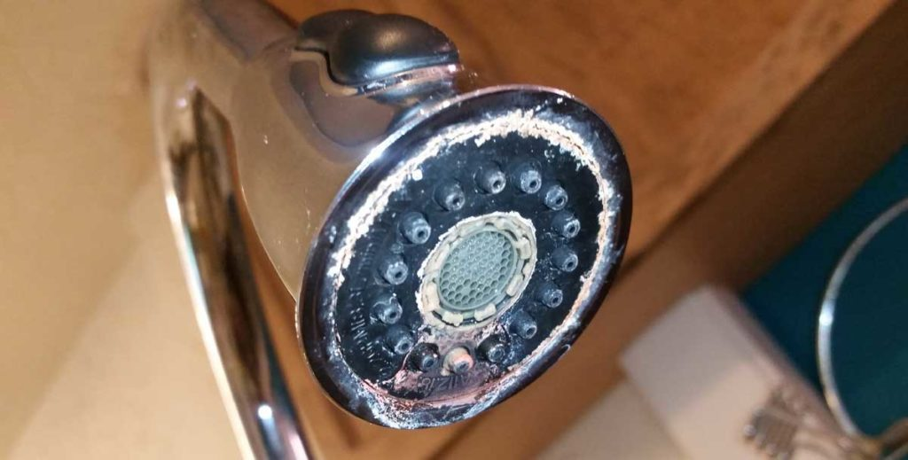 Limescale build-up on a kitchen sink faucet due to water hardness
