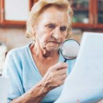 An elderly woman examines her Toronto water bill with a magnifying glass