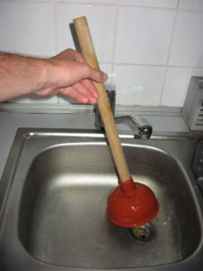 Sink plunger being held over a kitchen sink